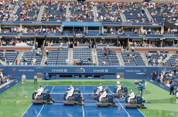 epa04929161 Workers dry the court as rain falls on Arthur Ashe Stadium just minutes before Roger Federer of Switzerland and Novak Djokovic of Serbia were to arrive on court for the men's final on the fourteenth day of the 2015 US Open Tennis Championship at the USTA National Tennis Center in Flushing Meadows, New York, USA, 13 September 2015. The US Open runs through 13 September, which is a return to a 14-day schedule.  EPA/ANDREW GOMBERT