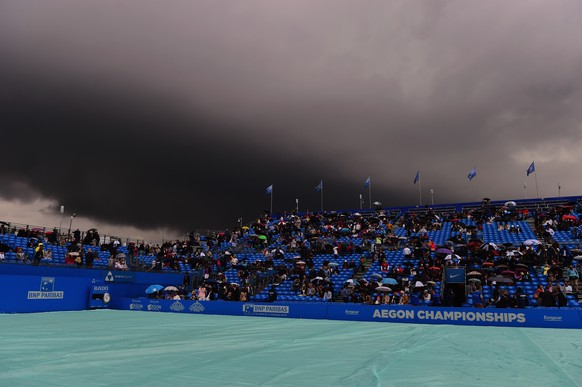 LONDON, ENGLAND - JUNE 20:  Spectators shelter from the rain as a dark rain cloud makes its way over centre court during the men's singles semi-final match between Andy Murray of Great Britain and Viktor Troicki of Serbia during day six of the Aegon Championships at Queen's Club on June 20, 2015 in London, England.  (Photo by Shaun Botterill/Getty Images)