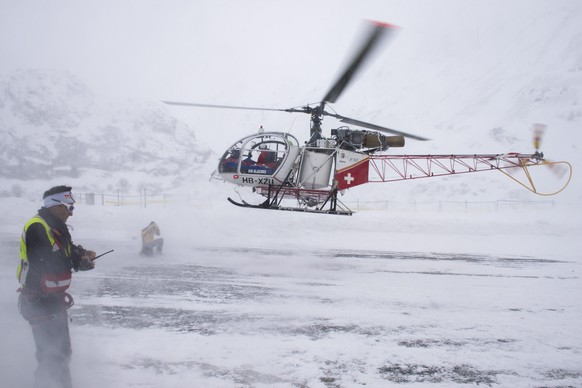 epa04630974 A rescue helicopter lands near the Grand Saint Bernard pass, Switzerland, 21 February 2015. Five ski tourers from Italy have been hit by an avalanche at the St. Bernard pass in Switzerland. All have been found but three of the gravely hurt died in the hospital.  EPA/MAXIME SCHMID