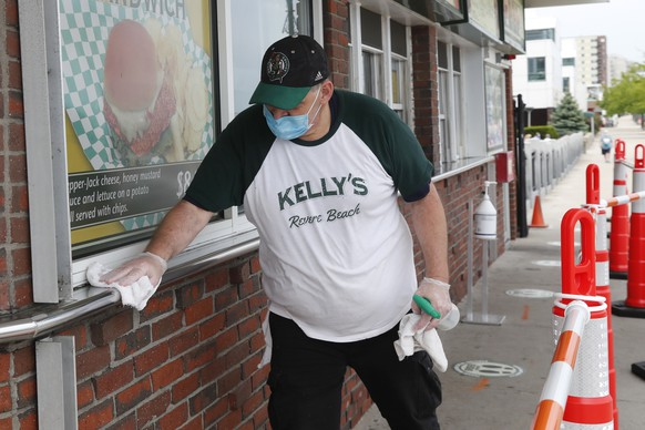 Chris Dotoli wipes down surfaces, Wednesday, June 3, 2020, outside Kelly's Roast Beef in Revere, Mass. Kelly's is open for outside delivery of food in accordance with the state's coronavirus guidelines. (AP Photo/Elise Amendola)