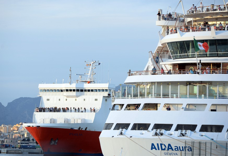 Ferry passengers look out from a cargo ship, left, as they arrive at port in Palma, Spain, Tuesday April 28, 2015, after they were evacuated from of a burning passenger ferry in Spanish waters between Palma de Mallorca and Valencia.  The fire broke out about 27 Km (17 miles) from the Mediterranean island city of Palma de Mallorca Tuesday, forcing 152 passengers to abandon the ship in lifeboats and injuring four crew members, Spanish officials said. The burning ferry is expected to sink and the cause of the fire is under investigation. (AP Photo/ Joan Llado)