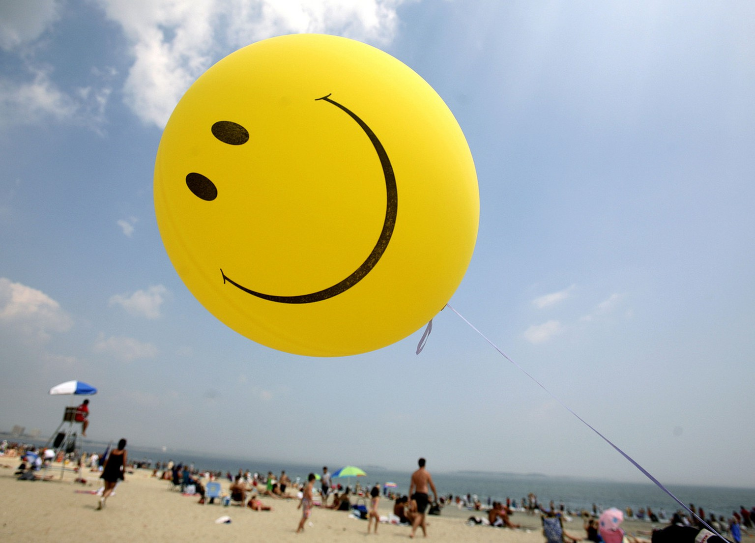 A smiley-face ballon floats over Revere Beach in Revere, Mass., as beachgoers head for the water, Sunday, July 16, 2006. (AP Photo/Michael Dwyer)