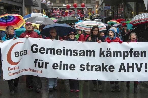 """Kundgebungsteilnehmer tragen ein Transparent mit einem Schreibfehler (""""fuer eine 'strake' AHV"""") und Fahnen am traditionellen 1. Mai-Umzug am Tag der Arbeit, in Basel, am Sonntag, 1. Mai 2016. Der Tag der Arbeit steht dieses Jahr im Zeichen der AHV. Die Gewerkschaften stellen den 1. Mai unter das Motto """"Gemeinsam kaempfen - fuer eine starke AHV"""".  (KEYSTONE/Georgios Kefalas)  Workers and unionists march in the streets of Basel, during the labor day demonstration, Switzerland, Sunday, May 1, 2016. (KEYSTONE/Georgios Kefalas)"""