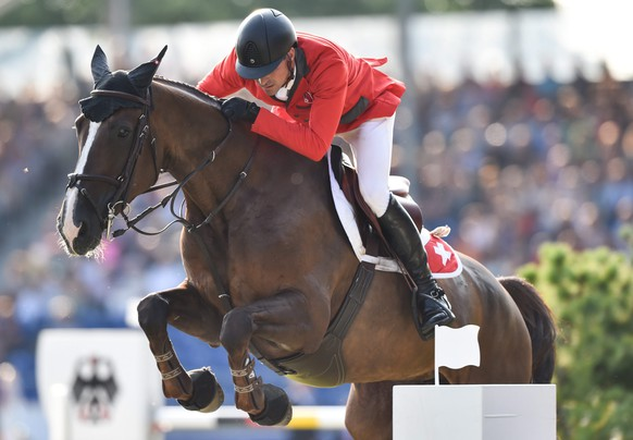 epa04891841 Romain Duguet of Switzerland jumps with his horse Quorida de Treho over an obstacle in the third round of the Show Jumping Team Final Competition during the FEI European Championships in Aachen, Germany, 21 August 2015.  EPA/FRISO GENTSCH