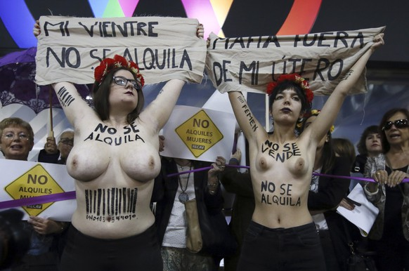 epa05946437 Two FEMEN activists holds banners reading 'My womb is not for rent' (L) and 'Mafia get out of my uterus' (R) as they protest outside the venue of the 'Surrofair' surrogate pregnancy fair in a hotel in Madrid, Spain, 06 May 2017. Several Lesbian, Gay, Bisexual and Transgender (LGBT) groups and women's right organizations gathered for a protest to express their anger about the fair. The 'Surrofair' from 06 to 07 May - according to their website - gathers experts and specialists from reproductive clinics to discuss the various possibilities and difficulties of surrogate pregnancy.  EPA/FERNANDO ALVARADO