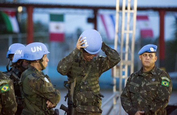 A United Nations peacekeeper from Brazil fixes his helmet before the end of operations ceremony for the United Nations Stabilization Mission in Port-au-Prince, Haiti, Thursday, Oct. 5, 2017. The U.N. peacekeeping mission in Haiti is coming to an official end on Oct. 15. Immediately afterward, the U.N. will start a new mission made up of international civilian police officers and civilians. (AP Photo/Dieu Nalio Chery)