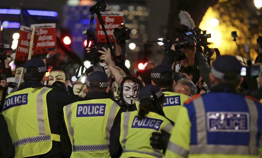 Police try and block masked demonstrators as they march in central London during the Million Mask protest march on Thursday Nov. 5, 2015. Thousands of people dressed in Guy Fawkes masks are being met by 'significant policing operation', including thousands of extra officers to tackle expected unrest in this annual march that coincides with the Nov. 5 Bonfire Night celebration.  (AP Photo/Tim Ireland)