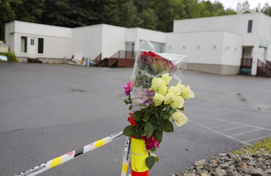 Flowers are left by a police cordon outside Al-Noor Islamic Centre Mosque in Baerum, Norway, Monday Aug. 12, 2019, after an attack at the mosque on Saturday. The defense lawyer for a suspected gunman accused of an attempted terrorist attack on an Oslo mosque and to having killed his teenage stepsister says her client