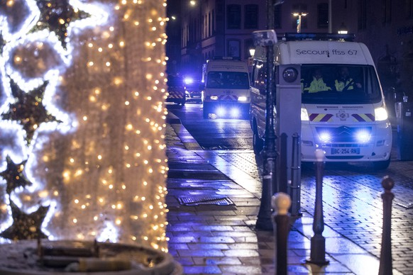 Police vehicles move at the center of the city of Strasbourg following a shooting, eastern France, Tuesday Dec. 11, 2018. A man who had been flagged as a possible extremist sprayed gunfire near the city of Strasbourg's famous Christmas market Tuesday, killing three people, wounding 12 and sparking a massive manhunt. France immediately raised its terror alert level.(AP Photo/Jean-Francois Badias)