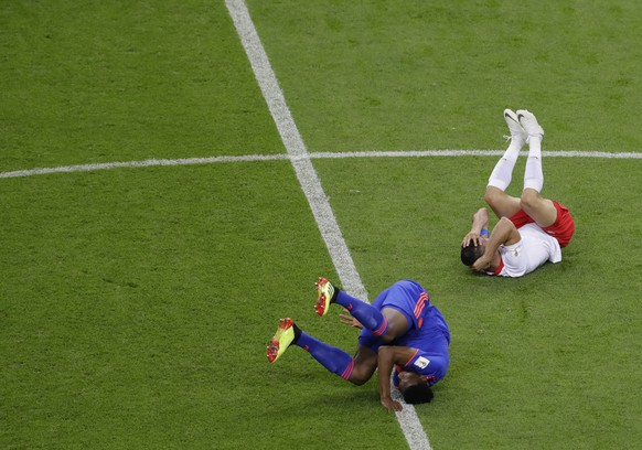Colombia's Yerry Mina, left, and Poland's Robert Lewandowski fall to the ground after colliding during the group H match between Poland and Colombia at the 2018 soccer World Cup at the Kazan Arena in Kazan, Russia, Sunday, June 24, 2018. (AP Photo/Sergei Grits)