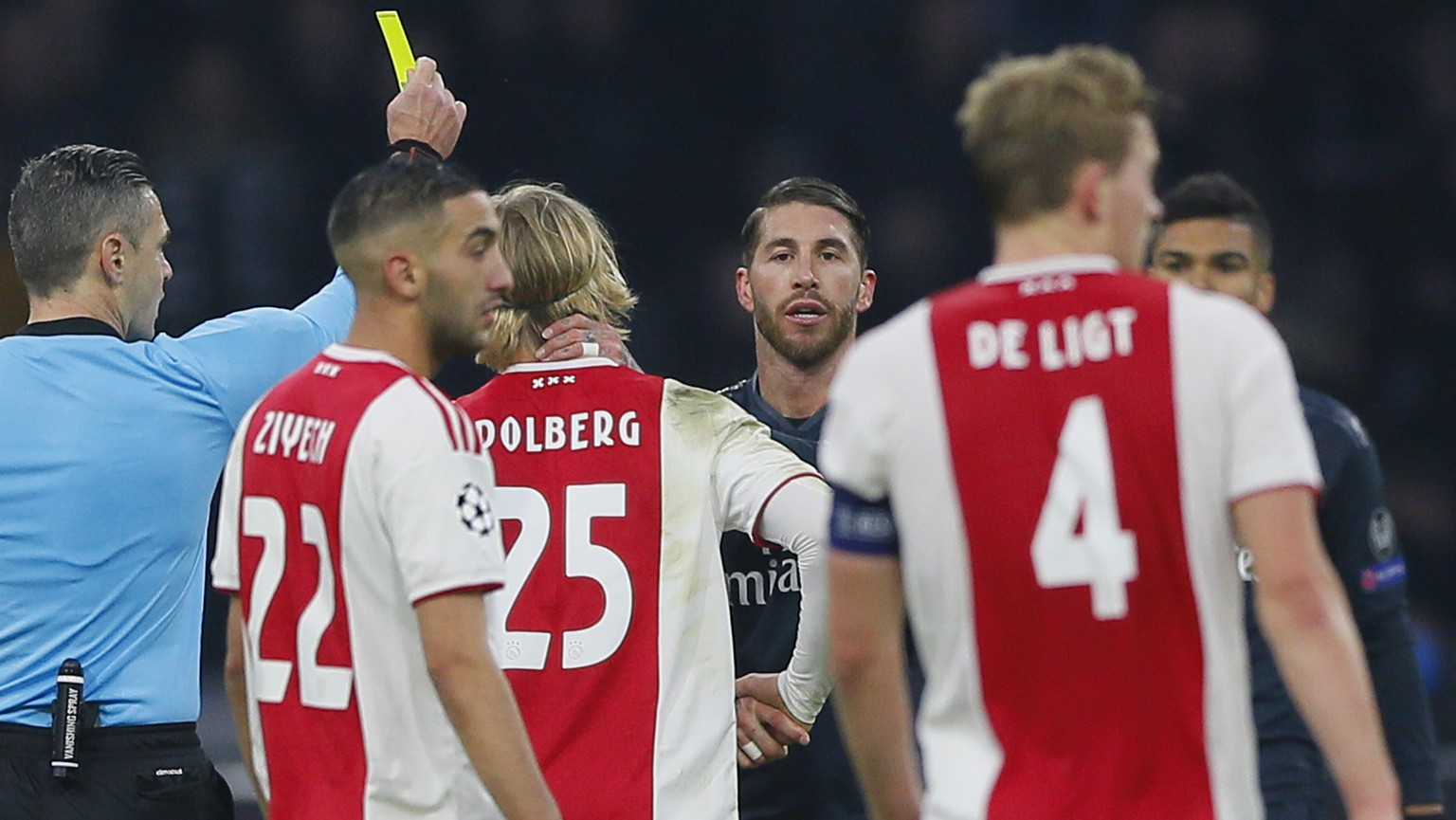 This Wednesday Feb. 13, 2019, image shows referee Damir Skomina, left, showing a yellow card to Real's Sergio Ramos, center, after a foul on Ajax's Kasper Dolberg during the first leg, round of sixteen, Champions League soccer match between Ajax and Real Madrid at the Johan Cruyff ArenA in Amsterdam, Netherlands. UEFA is investigating reported comments by Real Madrid captain Sergio Ramos that he intentionally got a yellow card to provoke a favorable Champions League ban. (AP Photo/Peter Dejong)