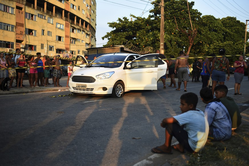 Residents gather to watch the death scene investigation where Evaldo dos Santos Rosa, the driver of a family car, was killed by armed forces, in the Guadalupe neighborhood, Rio de Janeiro, Brazil, Sunday, April 7, 2019. Authorities say soldiers mistook the car driven by Santos Rosa for that of criminals and was hit by 80 shots fired by members of the armed forces. Rosa was killed and his wife's stepfather wounded. Relatives say his wife, 7-year-old son and another woman were unharmed.(AP Photos/Fabio Teixeira)