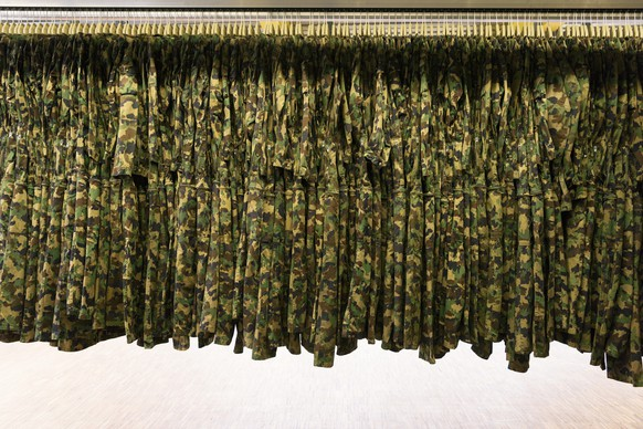 ZUM TEXTILCENTER DER SCHWEIZER ARMEE IN THUN  STELLEN WIR IHNEN HEUTE, MITTWOCH, 08. JUNI 2016, FOLGENDES BILDMATERIAL ZUR VERFUEGUNG --- Camouflage clothing is hung on coathangers before being checked and repaired at the textile center of the Swiss Armed Forces' logistics center in Thun, canton of Berne, Switzerland, on April 21, 2016. (KEYSTONE/Christian Beutler)