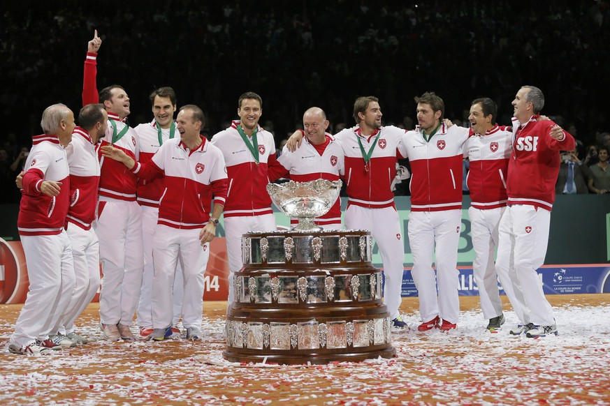 Switzerland's team members celebrate next to the Davis Cup trophy after winning the Davis Cup tennis tournament final match against France at the Pierre-Mauroy stadium in Villeneuve d'Ascq, near Lille, November 23, 2014. Roger Federer beat Richard Gasquet on Sunday to give Switzerland their first Davis Cup title with a 3-1 victory over hosts France in the final.          REUTERS/Gonzalo Fuentes (FRANCE  - Tags: SPORT TENNIS)