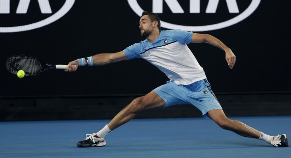 Croatia's Marin Cilic reaches for a forehand return to Australia's Bernard Tomic during their first round match at the Australian Open tennis championships in Melbourne, Australia, Monday, Jan. 14, 2019. (AP Photo/Kin Cheung)