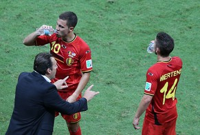 epa04294619 Belgium's coach Marc Wilmots (L) talks to his players Eden Hazard and Dries Mertens during a cooling break during the FIFA World Cup 2014 round of 16 match between Belgium and the USA at the Arena Fonte Nova in Salvador, Brazil, 01 July 2014.  