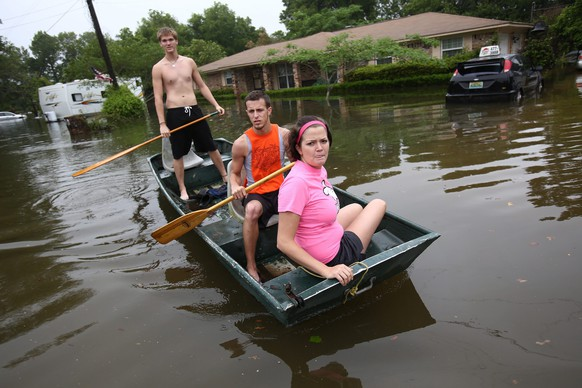 epaselect epa04186744 Shani Barlov (R) rides through the flooded streets of her neighborhood with her husband Nathan (C) and her brother Chip Walker, 16, in Pensacola, Florida, USA, 30 April 2014. The flooding stretches throughout the Gulf Coast, with parts of Florida under a state of emergency.  EPA/DAN ANDERSON