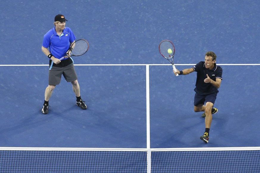 Mats Wilander, right, returns a shot to John McEnroe and James Blake, alongside Jim Courier during an exhibition doubles match at the U.S. Open tennis tournament, Thursday, Sept. 4, 2014, in New York. (AP Photo/John Minchillo)