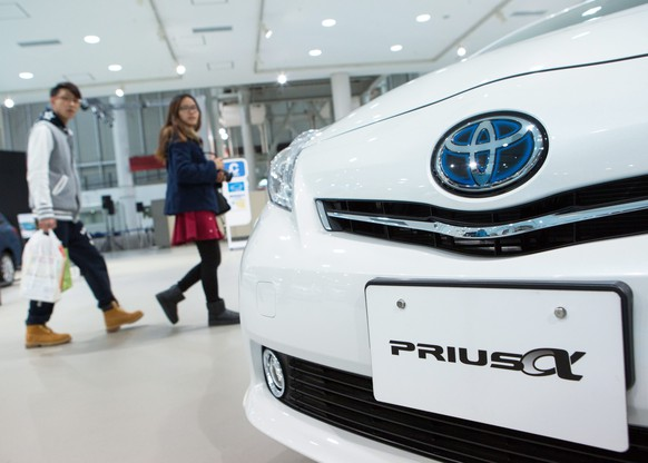 epa04847526 (FILE) A file picture dated 12 February 2014 of visitors walking past a Toyota Prius vehicle at a showroom in Tokyo, Japan. Toyota Motor Corp is recalling 625,000 hybrid vehicles globally to repair a software glitch, the carmaker said 15 July 2015. Models affected by the latest recall include certain Prius V vehicles, also sold as Prius Alpha and Prius+ in some regions.  EPA/CHRISTOPHER JUE *** Local Caption *** 51226688