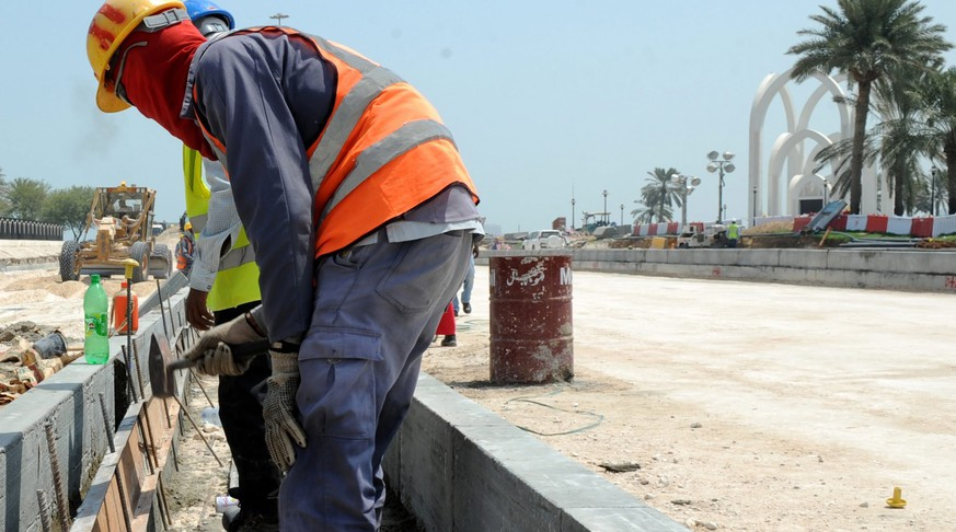epa03895985 Foreign laborers work at the construction site for a new corniche road in Doha, Qatar, 04 October 2013. Recent media reports said immigrant workers on projects for the World Cup 2022 have been subject to abuse and harsh working conditions. An investigation by Britain's Guardian newspaper said 44 Nepalis had died in Qatar from 04 June to 08 August.  EPA/STR