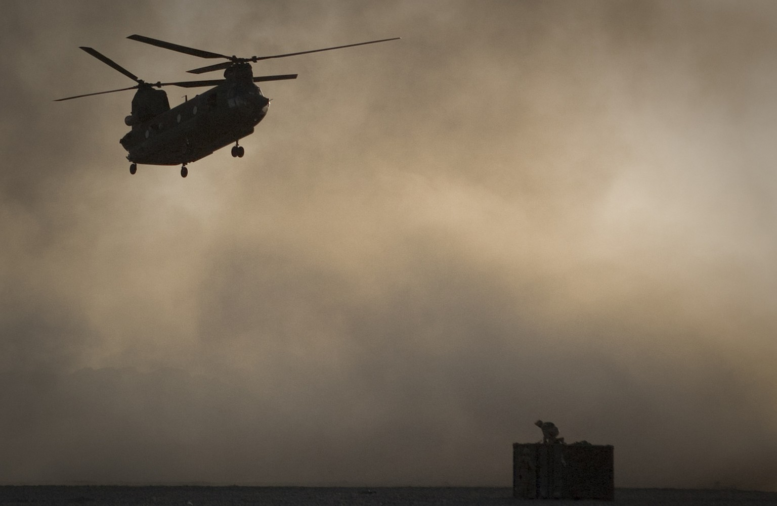 A US Marine tries to take cover, perched on a container, trying to shelter from the dust as a Chinook helicopter arrives to pick up supplies at Forward Operating Base Edi in the Helmand Province of southern Afghanistan, Thursday, June 9, 2011.   (AP Photo/Anja Niedringhaus)