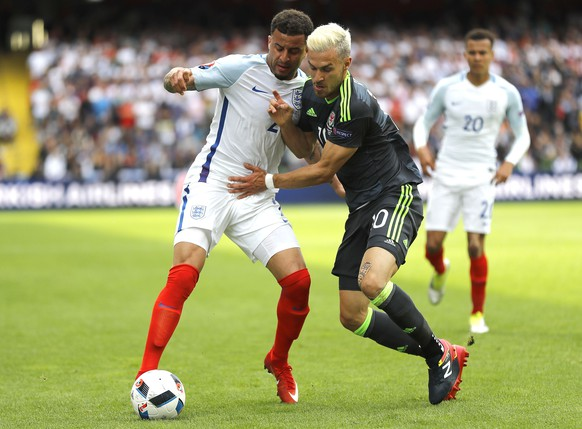 England's Kyle Walker, left, and Wales' Aaron Ramsey challenge for the ball during the Euro 2016 Group B soccer match between England and Wales at the Bollaert stadium in Lens, France, Thursday, June 16, 2016. (AP Photo/Frank Augstein)