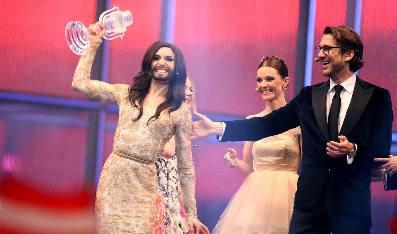 epa04200440 Conchita Wurst representing Austria (L) celebrates near the presenters Lise Rønne (2-R) and Nikolaj Koppel after winning the grand final of the 59th Eurovision Song Contest (ESC) in Copenhagen, Denmark, 10 May 2014.  EPA/JOERG CARSTENSEN