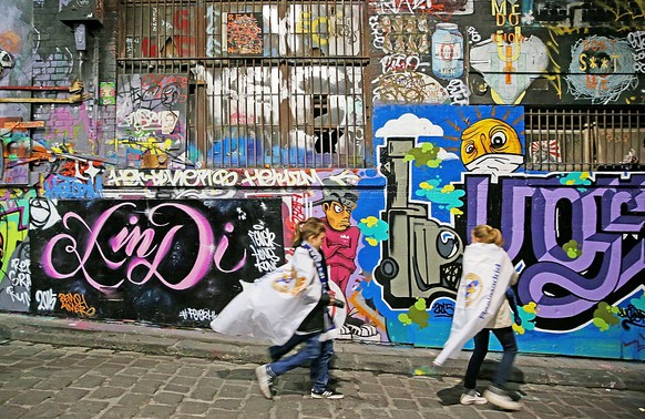 MELBOURNE, AUSTRALIA - JULY 24:  Real Madrid supporters walk down Hosier Lane past graffiti as they make their way to the MCG to attend the International Champions Cup match between Real Madrid and Manchester City at the Melbourne Cricket Ground on July 24, 2015 in Melbourne, Australia.  (Photo by Scott Barbour/Getty Images)