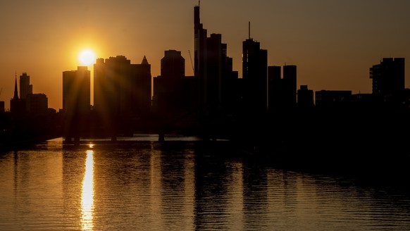 The buildings of the banking district near to the river Main as the sun sets in Frankfurt, Germany, Monday, April 6, 2020. Due to the coronavirus the economy worldwide expect heavy losses. (AP Photo/Michael Probst)