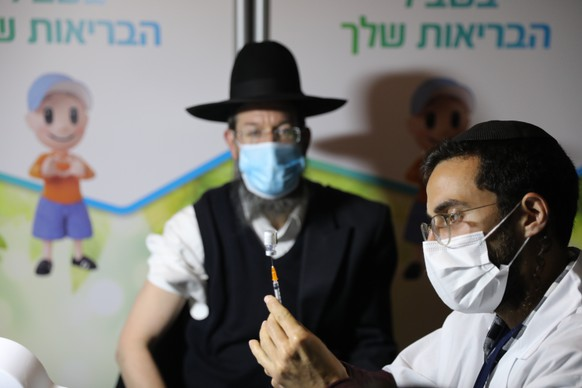 epa08937702 An ultra-orthodox Jewish man receives a coronavirus COVID-19 pandemic vaccine by a male nurse in Jerusalem, Israel, 14 January 2021. Media report that Israel is on a massive nationwide COVID-19 vaccination campaign, with more than two million people already got the first dose.  EPA/ABIR SULTAN