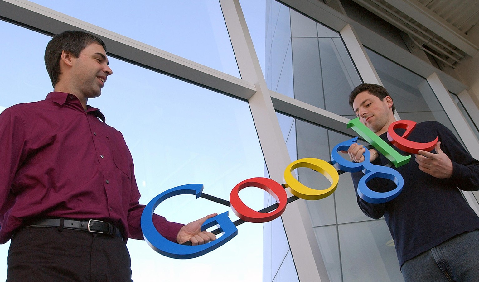 FILE - In this Jan. 15, 2004 file photo, Google co-founders Larry Page, left, and Sergey Brin pose for photos at their company's headquarters in Mountain View, Calif. Google's IPO 10 years ago launched the company on a trajectory that continues to reshape its business and much of the world in its orbit. (AP Photo/Ben Margot, File)