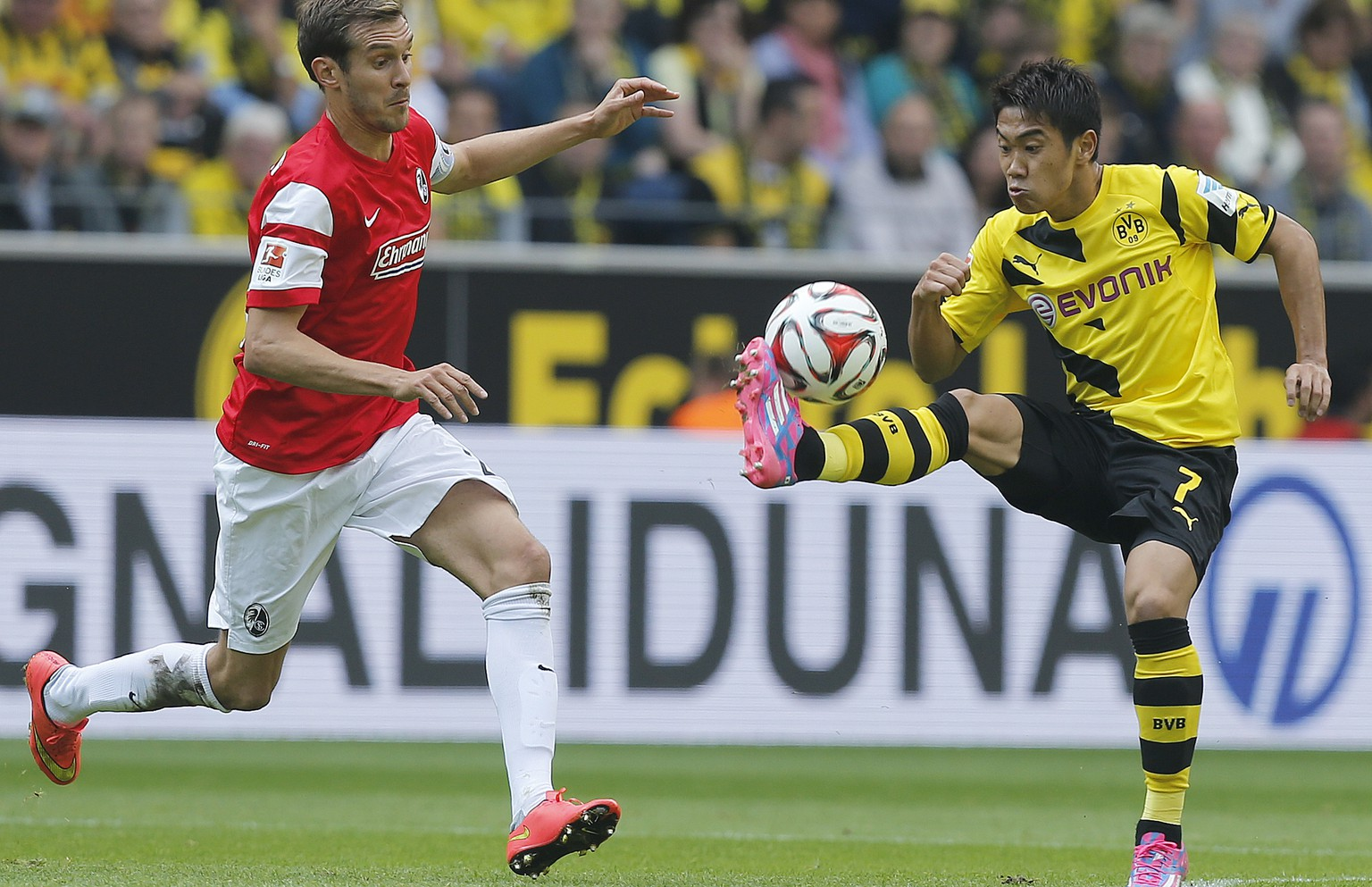 Dortmund's Shinji Kagawa from Japan, right, and Freiburg's Julian Schuster challenge for the ball during the German first division Bundesliga soccer match between BvB Borussia Dortmund  and SC Freiburg in Dortmund, Germany, Saturday, Sept. 13, 2014. (AP Photo/Frank Augstein)
