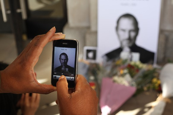 LONDON, ENGLAND - OCTOBER 06:  A man uses an iphone to photograph tributes to Apple Computer co-founder Steve Jobs outside The Apple Store in Covent Garden on October 6, 2011 in London, England. Jobs, 56, passed away after a long battle with pancreatic cancer. Jobs co-founded Apple in 1976 and is credited, along with Steve Wozniak, with marketing the world's first personal computer in addition to the popular iPod, iPhone and iPad.  (Photo by Peter Macdiarmid/Getty Images)