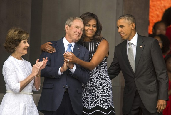 epa05603382 YEARENDER 2016 SEPTEMBER US First Lady Michelle Obama (2-R) hugs former President George W. Bush (2-L) while President Barack Obama (R) and former First Lady Laura Bush (L) look on at the opening of the Smithsonian's National Museum of African American History and Culture in Washington, DC, USA, 24 September 2016. The opening ceremony of the 400,000-square-foot museum attracted thousands of attendees.  EPA/Jim Lo Scalzo