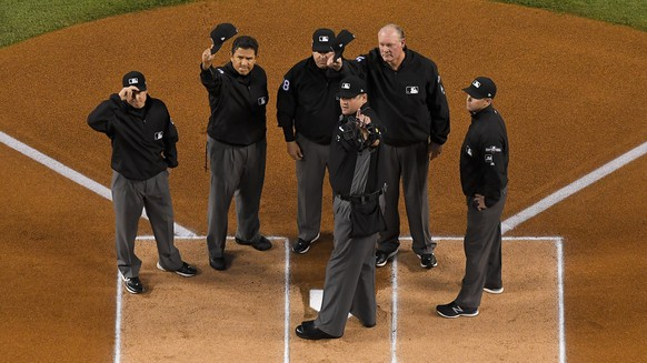 The umpires wave before Game 2 of a baseball National League Division Series between the Los Angeles Dodgers and the Washington Nationals on Friday, Oct. 4, 2019, in Los Angeles. (AP Photo/Mark J. Terrill)