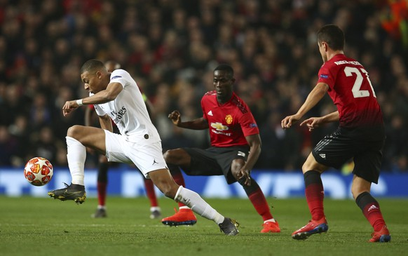 Paris Saint Germain's Kylian Mbappe, left controls the ball as Manchester United's Ander Herrera, right, looks on during the Champions League round of 16 soccer match between Manchester United and Paris Saint Germain at Old Trafford stadium in Manchester, England, Tuesday, Feb. 12, 2019. (AP Photo/Dave Thompson)