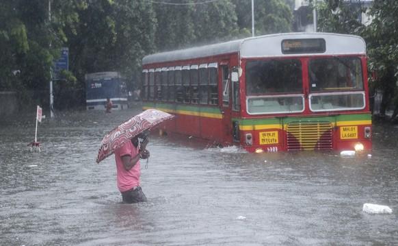 A man makes his way across a flooded street during heavy rains in Mumbai, India, Wednesday, June 9, 2021. (AP Photo/ Rafiq Maqbool)
