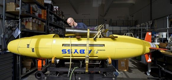 Electrical engineer Lars Triebe inspects the Autonomous Underwater Vehicle (AUV) 'Abyss' in preparation for operational service, at the Helmholtz Centre for Ocean Research Kiel (GEOMAR) in Kiel March 24, 2014. The 'Abyss', one of only three worldwide unmanned deep sea search submarines, may join the hunt for the missing Malaysia Airlines flight MH370. The submarine is designed to perform hydrographic reconnaissance in all parts of the ocean in depths up to 6000 meters and can stay submerged for up to 22 hours.   REUTERS/Fabian Bimmer (GERMANY - Tags: DISASTER MARITIME POLITICS SCIENCE TECHNOLOGY TPX IMAGES OF THE DAY) - RTR3IDIG