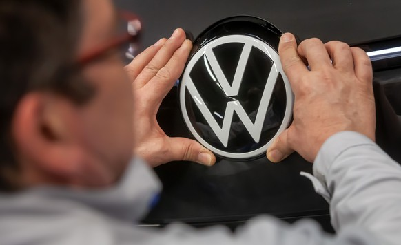 epa08247050 A Volkswagen employee fixes the VW logo on a Volkswagen ID.3 car in the assembly line during the production of the electric car at the Volkswagen (VW) vehicle factory in Zwickau, Germany, 25 February 2020. The Volkswagen annual press conference will be held on 17 March 2020 in Wolfsburg.  EPA/UWE MEINHOLD