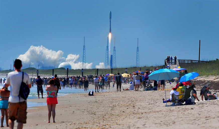 People on the Canaveral National Seashore watch a United Launch Alliance Atlas V rocket lift off from Cape Canaveral Air Force Station in Cape Canaveral, Fla. on Wednesday, May 20, 2015. The rocket is carrying the X-37B space plane for the U.S. Air Force as well as 10 CubeSats and the Planetary Society's LightSail Mission. (Craig Rubadoux/Florida Today via AP)