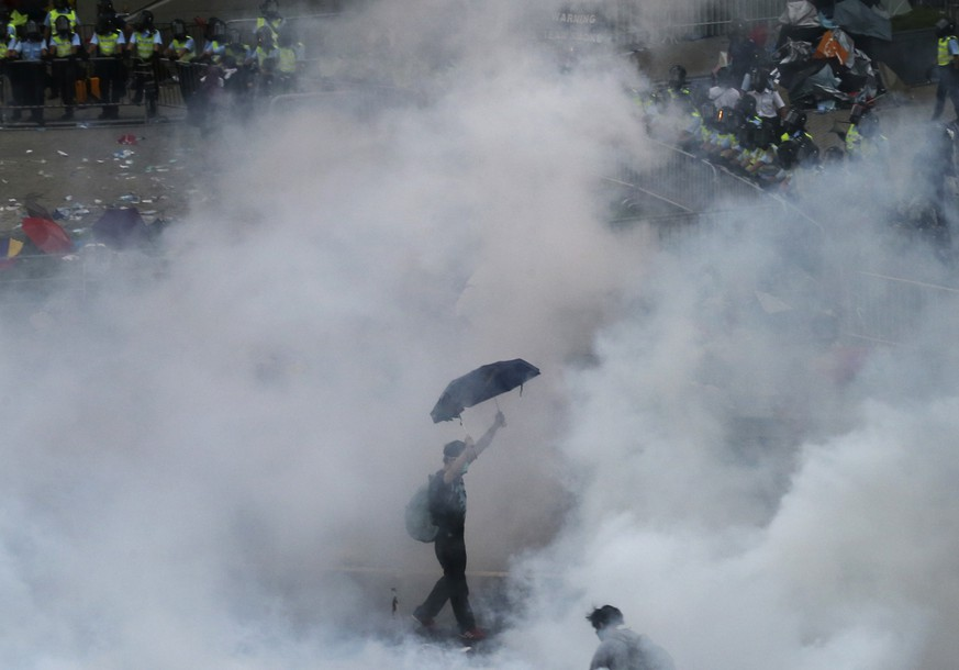 A protester walks in tear gas fired by riot policemen after thousands of protesters blocking the main street to the financial Central district outside the government headquarters in Hong Kong September 28, 2014. Hong Kong police fired repeated volleys of tear gas to disperse pro-democracy protests on Sunday and baton-charged the crowd blocking a key road in the government district after official warnings against illegal demonstrations.   REUTERS/Stringer  (CHINA - Tags: POLITICS CIVIL UNREST) HONG KONG OUT. NO COMMERCIAL OR EDITORIAL SALES IN HONG KONG