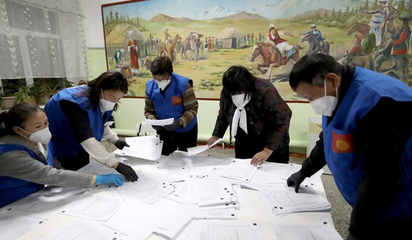 epa08720489 Members of Kyrgyz local election commission count ballots after the closure of a polling station in the village of Gornaya Maevka, 30km from Bishkek, Kyrgyzstan, 04 October 2020.  EPA/IGOR KOVALENKO