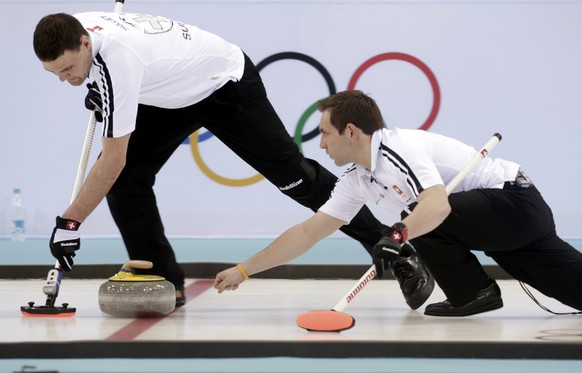 Switzerland's skip Sven Michel (R) delivers a stone as Sandro Troillet sweeps ahead of it during their men's curling round robin session game against China at the 2014 Sochi Olympics in the Ice Cube Curling Center in Sochi February 12, 2014. REUTERS/Ints Kalnins (RUSSIA  - Tags: SPORT OLYMPICS SPORT CURLING)