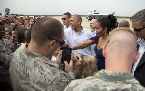 President Barack Obama and first lady Michelle Obama greet members of the military and their family as they arrive at Air Station Cape Cod, in Mass., Saturday, Aug. 6, 2016. The president and his family are vacationing in the Massachusetts island of Martha's Vineyard. (AP Photo/Manuel Balce Ceneta)