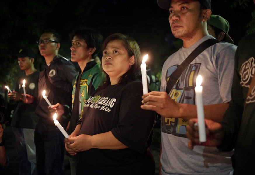 Activists hold candles during a vigil for the victims of the attacks in Surabaya, in Jakarta, Indonesia, Monday, May 14, 2018. An Indonesian family brought its 8-year-old daughter to a suicide bomb attack it launched Monday on the police headquarters in the country's second-largest city, authorities said, a day after members of another family conducted coordinated suicide bombings on three city churches that killed a number of people. (AP Photo/Dita Alangkara)