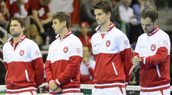 The Swiss tennis players Michael Lammer, Henri Laaksonen, Adrien Bossel and Swiss Davis Cup Team captain Severin Luethi, from left, listen the national hymn before the fourth match of the Davis Cup World Group - First Round, 1/8 final tennis match Belgium against Switzerland, at the Country Hall, in Liege, Belgium, Sunday, March 8, 2015. Switzerland will face Belgium in its first tie as a reigning Davis Cup champion. (KEYSTONE/Laurent Gillieron)
