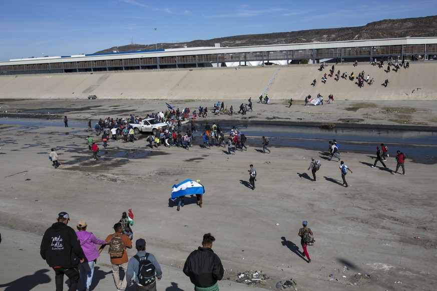 Migrants walk across a riverbank at the Mexico-U.S. border after getting past a line of Mexican police at the Chaparral border crossing in Tijuana, Mexico, Sunday, Nov. 25, 2018, as they try to reach the U.S. The mayor of Tijuana has declared a humanitarian crisis in his border city and says that he has asked the United Nations for aid to deal with the approximately 5,000 Central American migrants who have arrived in the city. (AP Photo/Rodrigo Abd)