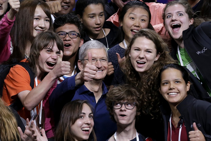 Apple CEO Tim Cook, center, poses for photos after speaking at the Apple Worldwide Developers Conference in San Francisco, Monday, June 8, 2015. The maker of iPods and iPhones announced Apple Music, an app that combines Beats 1, a 24-hour, seven-day live radio station, with an on-demand music streaming service. (AP Photo/Jeff Chiu)