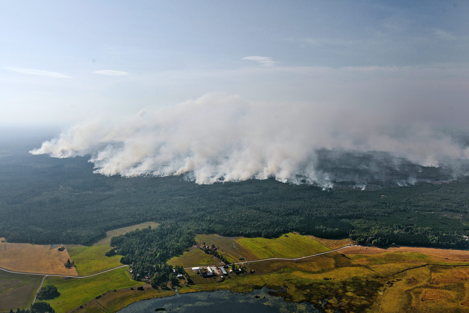 epa04340806 A photograph made available on 04 August 2014 shows smoke billowing as the wildfire front nears the village of Rorbo near Sala, Sweden, 03 August 2014. The fire, covering thousands of hectares, is in its fifth day and firefighters believe it will burn for weeks or even months. It is classified as the worst forest fire in Sweden's modern history.  EPA/JOCKE BERGLUND SWEDEN OUT