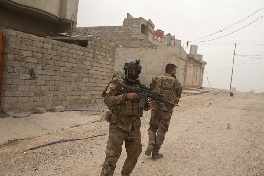In this Tuesday, Nov. 1, 2016 photo, Iraqi special forces soldiers try to find cover as they take fire from Islamic State militants in Gogjali, an eastern district of Mosul, Iraq. Iraqi special forces paused their advance in the eastern district of Mosul on Wednesday to clear a neighborhood of any remaining Islamic State militants, killing at least eight while carrying out house-to-house searches. (AP Photo/Marko Drobnjakovic)